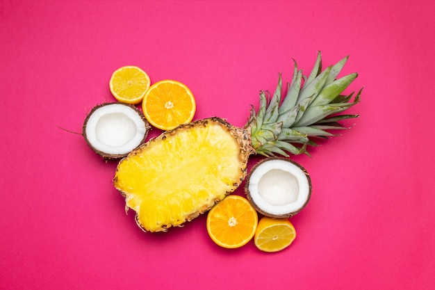 Fond de fruits ananas, noix de coco sur fond rose. fruits d'été. lay plat, vue de dessus, espace de copie Photo Premium