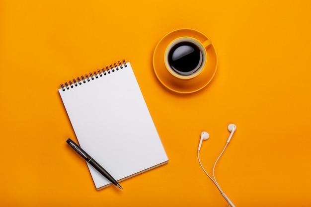 Sur un fond jaune, une tasse de café noir avec un bloc-notes et des écouteurs Photo Premium