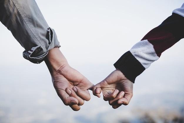 Fond de jour de valentine. heureux couple tenant les mains ensemble pour toujours l'amour. Photo gratuit