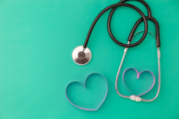 Fond de journée mondiale de la santé, stéthoscope et coeur de ruban rose sur fond vert, concept santé et fond médical Photo Premium