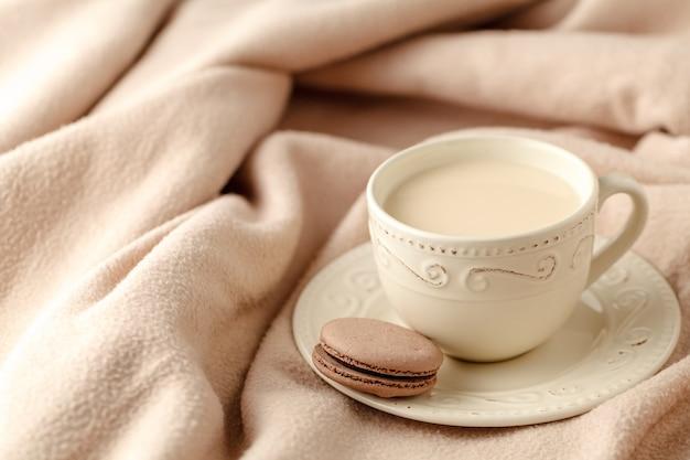 Fond De Maison D'hiver Confortable, Tasse De Café Chaud Avec Du Lait, Pull En Tricot Chaud Sur Fond De Lit Blanc, Ton Vintage. Concept De Style De Vie Photo Premium