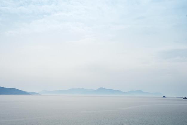 Fond de nature mystérieuse magnifique avec de l'océan contre les montagnes brumeuses Photo Premium