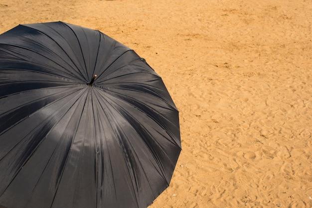 Fond Naturel Du Parasol Noir De La Plage De Sable Du Soleil. Photo Premium