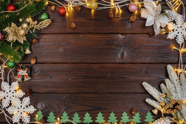 Le Fond De Noël En Bois Est Décoré Avec Un Décor De Fête, Des Lanternes, Des Flocons De Neige Et Des Branches De Sapin De Noël. Carte De Noël. Saison Des Vacances D'hiver. Bonne Année. Photo Premium