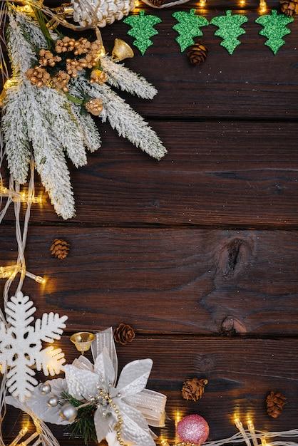 Le Fond De Noël En Bois Est Décoré Avec Un Décor De Fête, Des Lanternes, Des Flocons De Neige Et Des Branches De Sapin De Noël. Photo Premium
