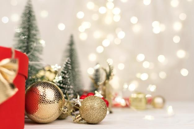 Fond De Noël, Boîte-cadeau Rouge Avec Un Arc D'or Sur Le Fond Du Bokeh De Noël. Copier L'espace Photo Premium