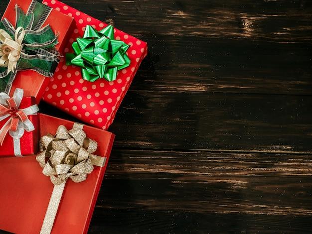 Fond De Noël Et Bonne Année. Vue De Dessus De La Belle Boîte-cadeau Rouge Avec Des Décorations D'arc Vert Et Or Brillant Sur Planche De Bois Sombre Photo Premium