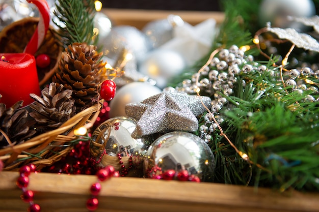 Fond De Noël. Branches De Sapin, Décor De Noël, Cônes, Boules Rouges Et Argentées, Perles Rouges Photo Premium