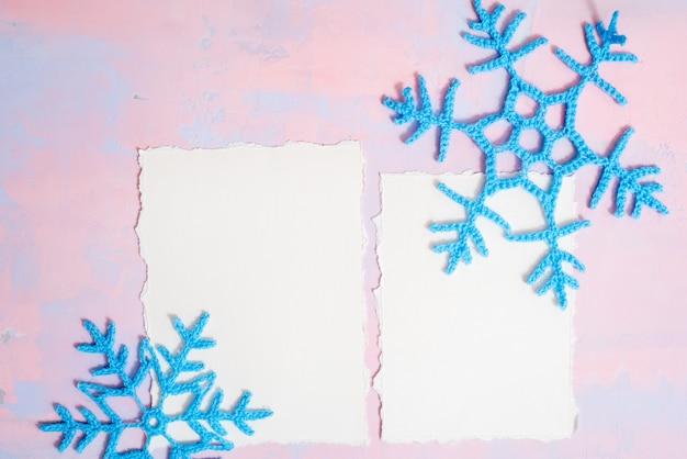Fond de noël avec cahier vierge, flocon de neige au crochet bleu, fait à la main sur un fond violet-rose. papier déchiré tendance. lay plat, vue de dessus. fond Photo Premium