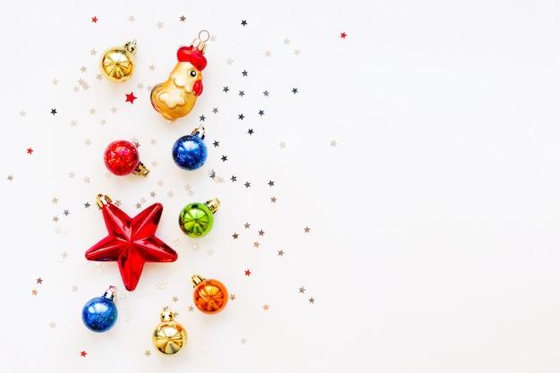 Fond de noël avec des décorations. boules colorées brillantes, étoile et confettis. lay plat, vue de dessus. place pour le texte. Photo Premium