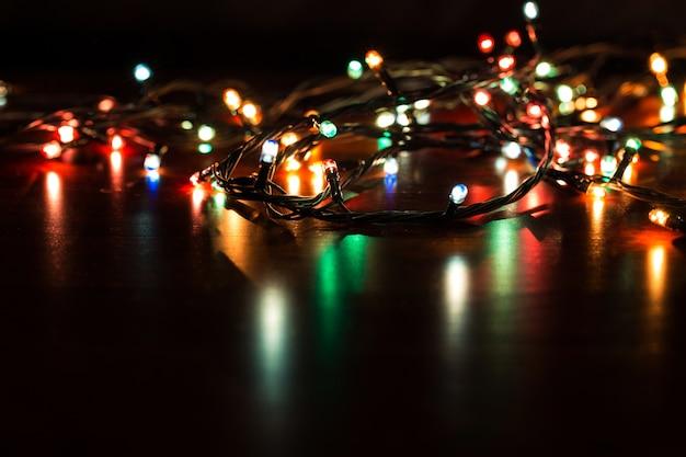 Fond de noël avec des lumières. lumières de noël colorées rougeoyantes sur fond noir. Photo Premium