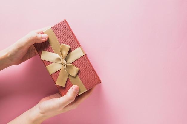 Fond De Noël Avec Les Mains Tenant La Boîte Actuelle Photo Premium