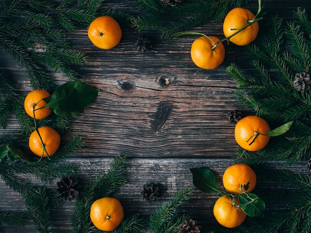 Fond de noël avec des mandarines, des branches de sapin et des pommes de pin. cadre de vacances d'hiver Photo Premium