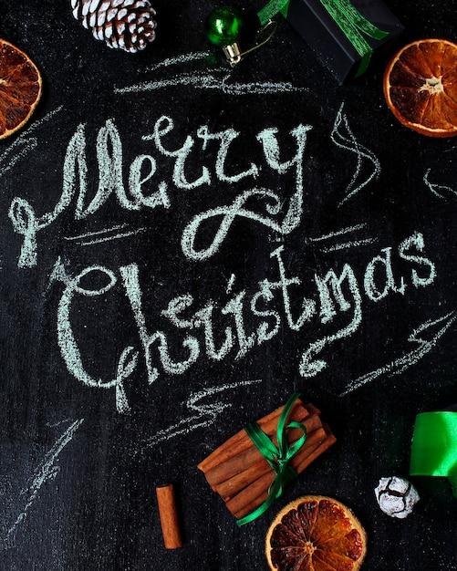 Fond de noël avec les mots joyeux noël, orange sec, pomme de pin blanche, boules vertes d'arbre de noël Photo Premium
