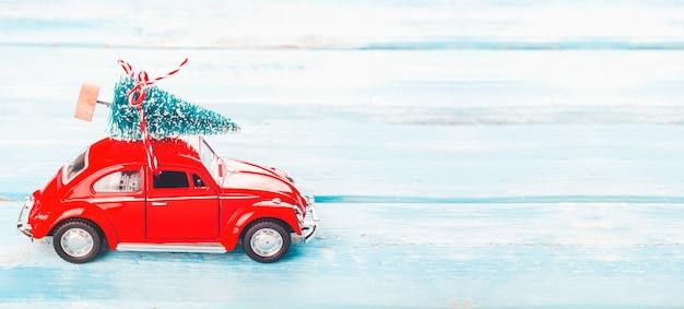 Fond de noël avec voiture rouge et arbre de noël Photo Premium