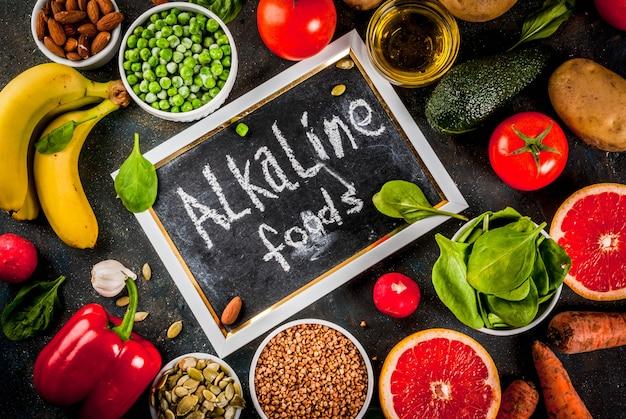 Fond de nourriture saine, produits de régime alcalins à la mode - fruits, légumes, céréales, noix. huiles, fond en béton bleu foncé ci-dessus Photo Premium