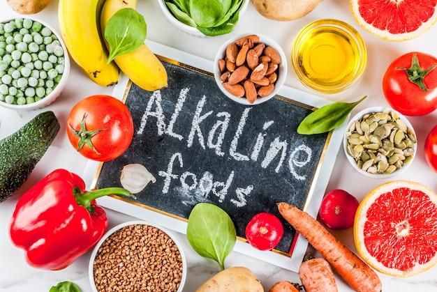 Fond de nourriture saine, produits de régime alcalins à la mode - fruits, légumes, céréales, noix. huiles, fond de marbre blanc ci-dessus Photo Premium
