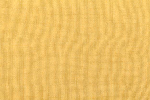 Fond ocre jaune clair issu d'une matière textile. tissu à texture naturelle. toile de fond. Photo Premium