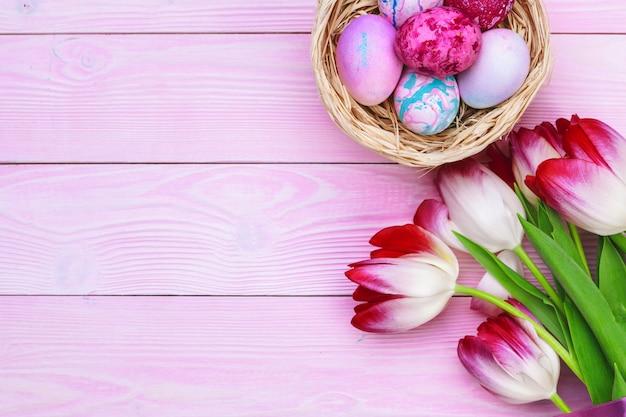 Fond de pâques avec des oeufs colorés et des tulipes sur bois rose. vue de dessus avec espace de copie Photo Premium