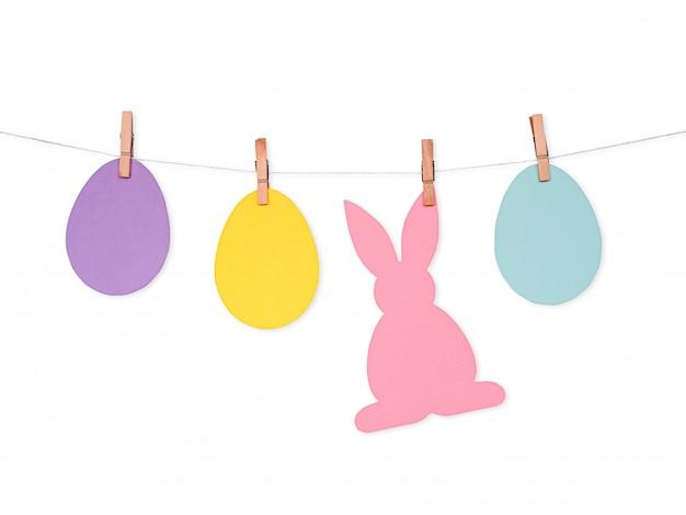 Fond de pâques avec des oeufs en papier coloré et le lapin sur corde Photo Premium