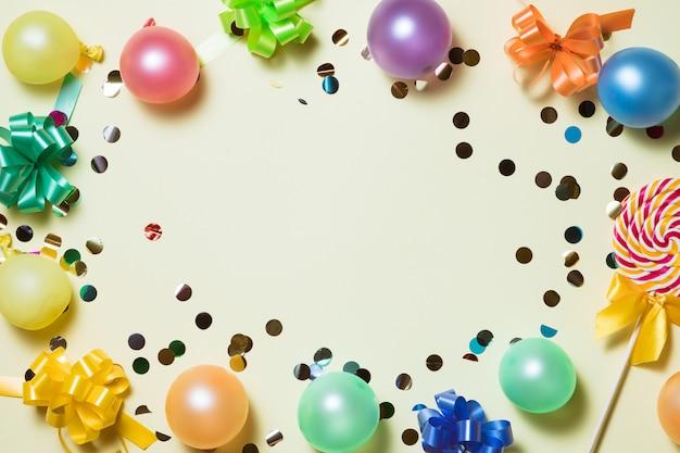 Fond pastel lumineux de fête d'anniversaire avec des banderoles, des confettis, des ballons sur le fond jaune. Photo Premium
