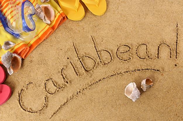Fond de plage avec une serviette et des tongs et le mot caraïbes écrit en sable Photo Premium