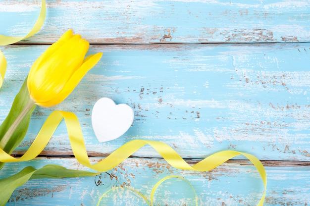 Fond de printemps avec une tulipe jaune avec ruban et coeur Photo Premium