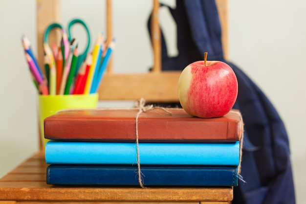 Fond de retour à l'école avec pile de livres et pomme rouge. Photo Premium