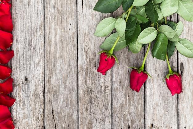 Fond romantique avec fleurs roses rouges sur une table rustique en bois avec la surface. Photo Premium