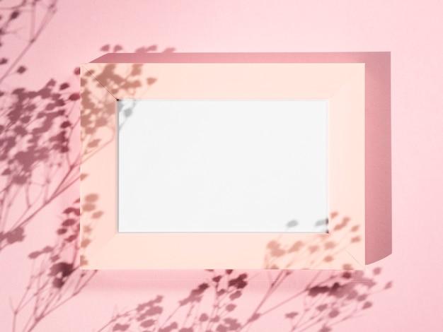 Fond rose avec un cadre photo rose et des ombres de branche Photo gratuit