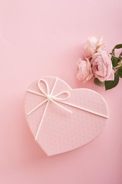 Fond rose avec des fleurs et une boîte cadeau Photo Premium