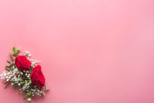Fond rose romantique avec des roses rouges et des fleurs Photo Premium