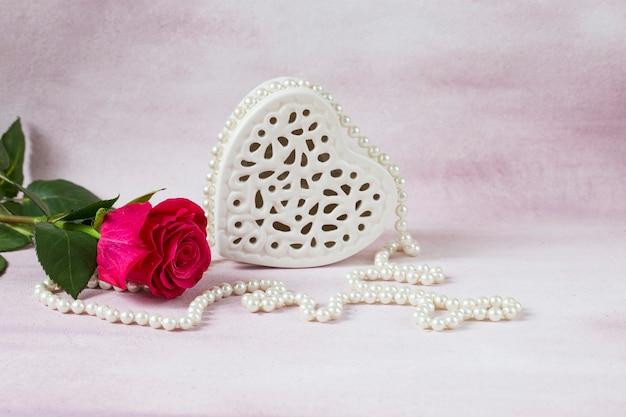 Sur fond rose, une rose rose vif, des perles et un coeur blanc en porcelaine Photo Premium