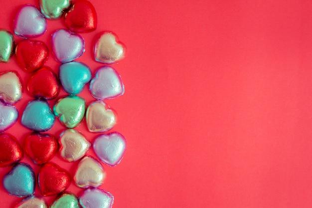 Fond rouge avec des repos de coeur multicolores Photo Premium