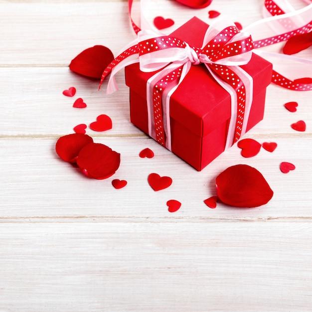 Fond De La Saint-valentin De Boîte-cadeau Et Pétales De Rose Sur Bois Blanc Photo Premium