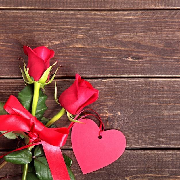 Fond De La Saint-valentin De L'étiquette-cadeau Et Des Roses Rouges Sur Bois Photo Premium