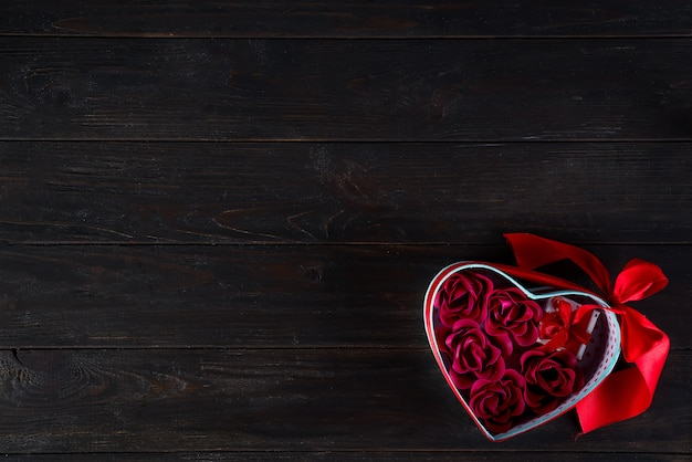 Fond saint-valentin avec mini cadeau et rose dans une boîte coeur Photo Premium