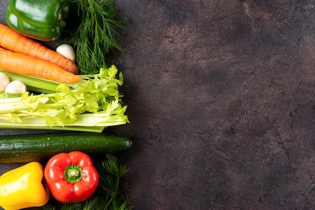 Fond sombre avec une bordure de légumes frais. vue de dessus. Photo Premium