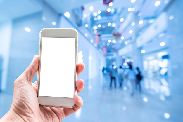 Fond de technologie, main tenant mobile avec écran vide et centre commercial floue Photo Premium