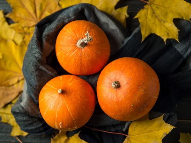 Fond de thanksgiving, citrouilles orange et feuilles d'automne sur un fond en bois foncé Photo Premium