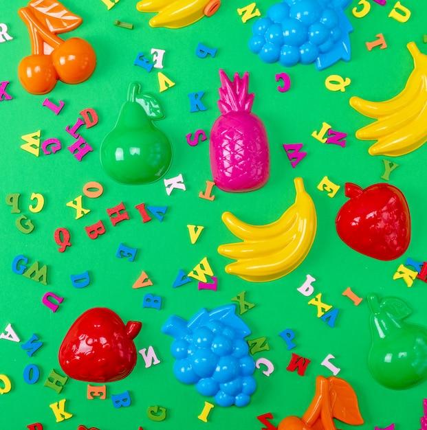 Fond Vert Avec Jouets En Plastique Pour Enfants Et Lettres Multicolores En Bois Photo Premium