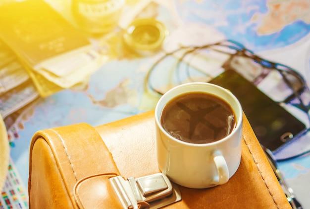 Fond le voyage, le reflet dans la tasse de café. carte. mise au point sélective. Photo Premium