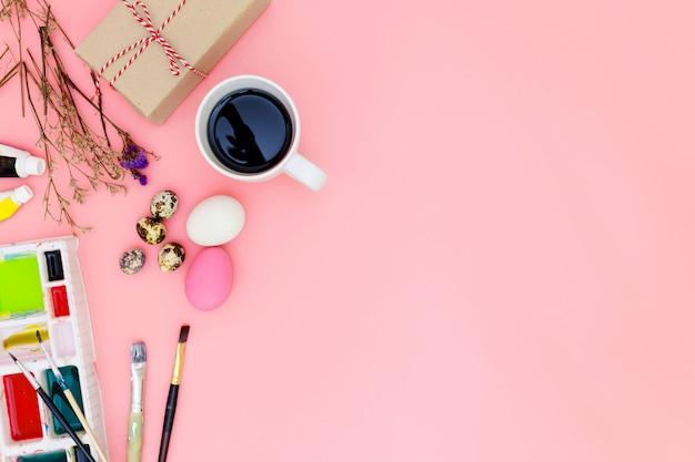 Fond de vue de dessus et jeu de peinture préparant pour pâques sur fond rose, oeufs de pâques Photo Premium