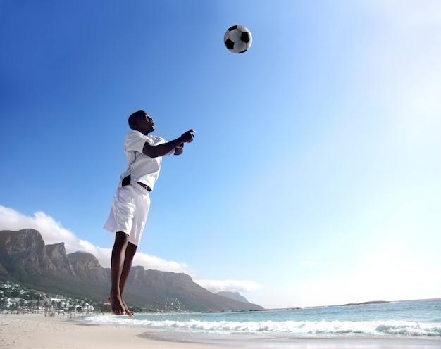 Football africain ou joueur de football en direction de la balle sur la plage Photo Premium