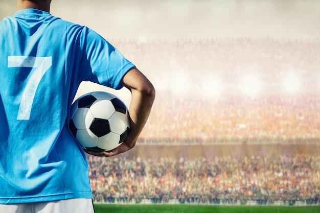 Football joueur de football dans le concept de l'équipe bleue tenant le ballon de soccer Photo Premium