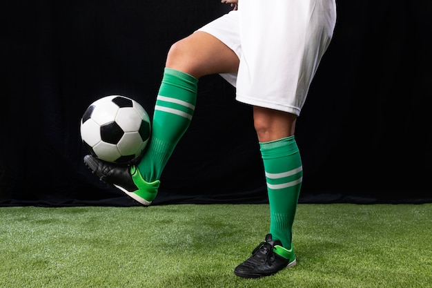 Football en tenue de sport avec ballon Photo gratuit