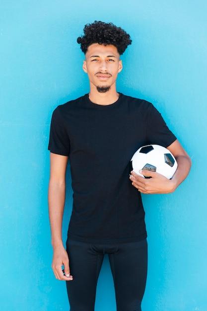 Footballeur Avec Ballon Sous Le Bras Près Du Mur Photo gratuit