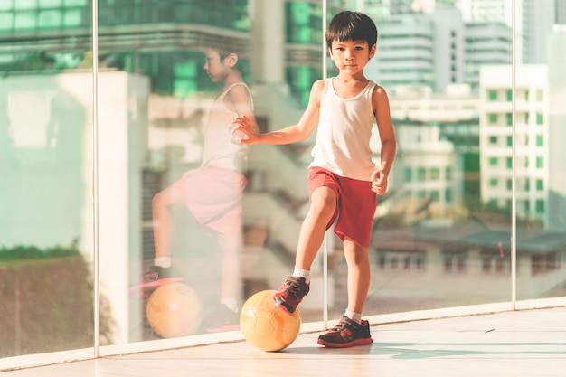 Footballeur garçon marche sur le ballon dans la salle Photo Premium