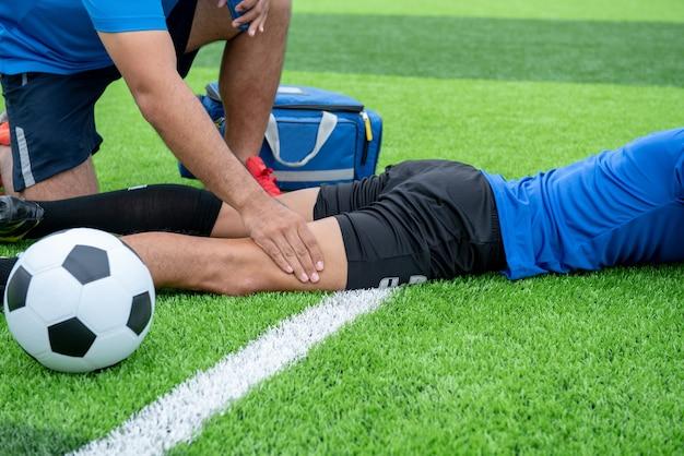 Footballeur vêtu d'une chemise bleue, un pantalon noir blessé dans la pelouse pendant la course. Photo Premium