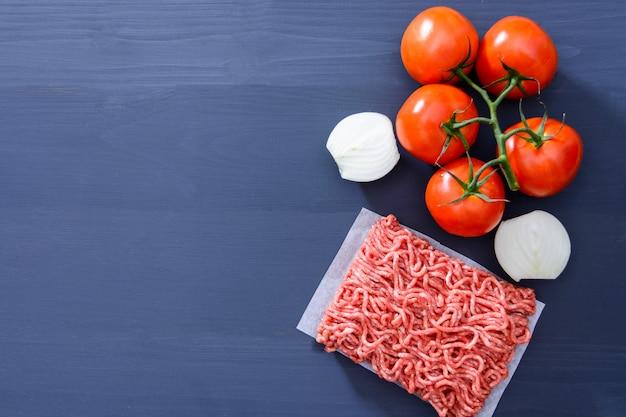 Forcemeat Avec Des Tomates Rouges Sur Une Branche Et Des Oignons émincés Sur Un Fond En Bois Gris Avec Espace De Copie Photo Premium